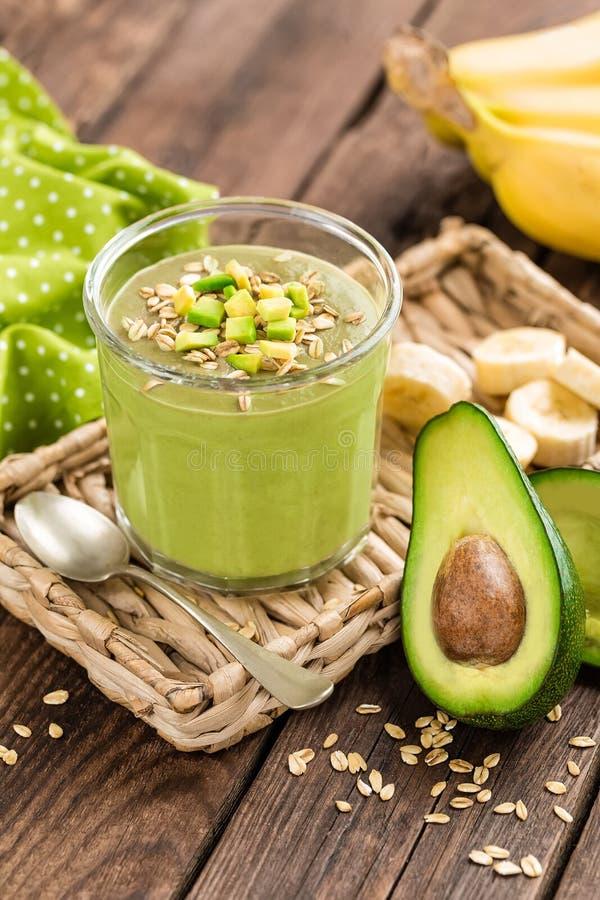 Avocado en banaan smoothie met haver met ingrediënten in glaskruik op houten achtergrond stock foto