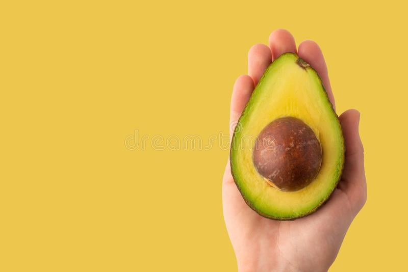 Avocado in a female hand is isolated on a yellow background, for design, horizontal photo, banner.  royalty free stock photography