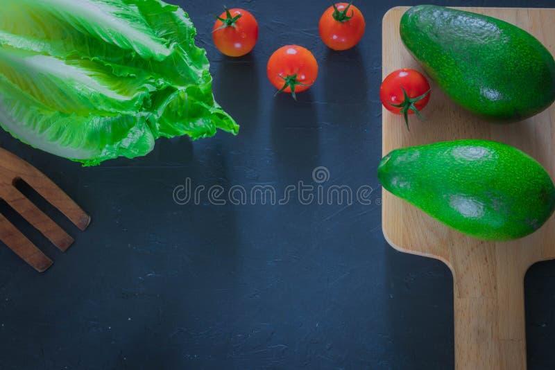 Avocado fresco su un tagliere con le foglie della lattuga su un fondo di legno Alimento sano Copi lo spazio fotografia stock libera da diritti