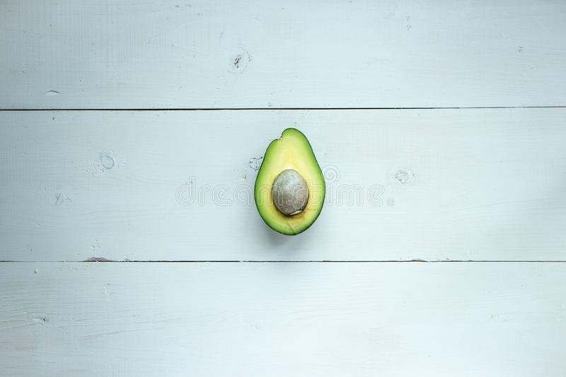 Avocado fruit cutted in half at rustic white wooden background, raw and vegan food photography. Green, fresh, organic and healthy food. Copy past and space for stock photos