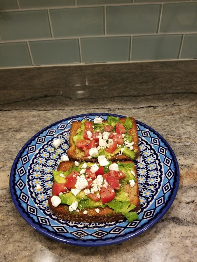 Avocado grzanka na połysku ceramicznym obsiadaniu na granitowym countertop obrazy stock
