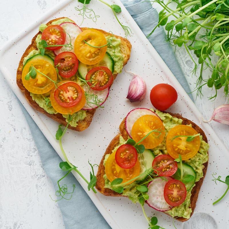 Avocado grzanka z czereśniowymi pomidorami i ziele, śniadanie zdjęcie stock