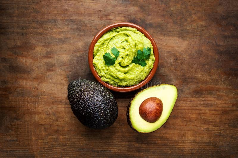 Avocado with guacamole sauce on a dark wood background. Half and stock photography