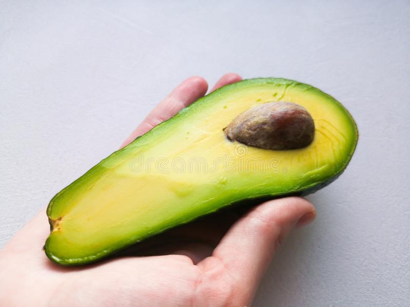 Avocado in hand, on white background. Man Proposing To Woman With Engagement Ring In Avocado. Closeup. Cut avocado.  royalty free stock photos