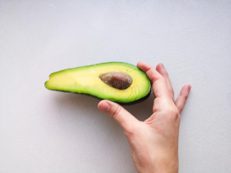 Avocado in hand, on white background. Man Proposing To Woman With Engagement Ring In Avocado. Closeup. Cut avocado.  stock images