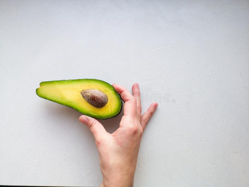 Avocado in hand, on white background. Man Proposing To Woman With Engagement Ring In Avocado. Closeup. Cut avocado stock photography