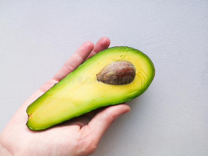 Avocado in hand, on white background. Man Proposing To Woman With Engagement Ring In Avocado. Closeup. Cut avocado.  royalty free stock photo