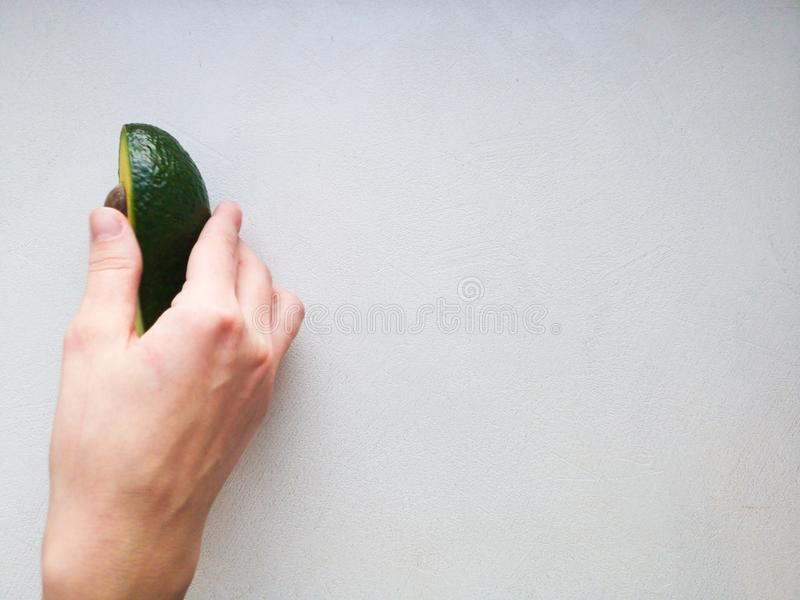 Avocado in hand, on white background. Man Proposing To Woman With Engagement Ring In Avocado. Closeup. Cut avocado.  stock photography