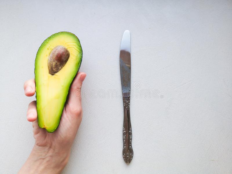 Avocado in hand, on white background. Man Proposing To Woman With Engagement Ring In Avocado. Closeup. Cut avocado.  royalty free stock image