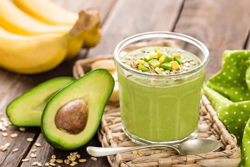 Avocado i banana smoothie z owsami z składnikami w szklanym słoju na drewnianym tle obrazy stock