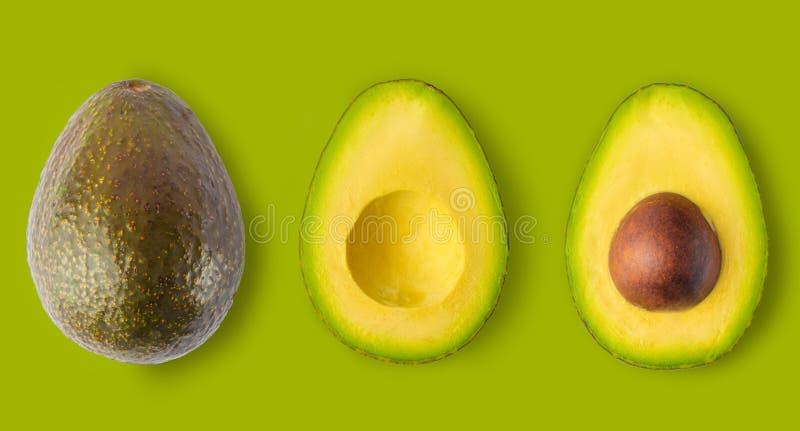 Avocado isolato su fondo verde Intero di avocado e due metà in una fila, isolata su un fondo verde, in grande immagine stock libera da diritti