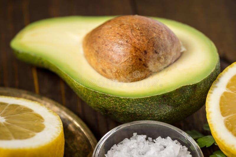 Avocado, limone e prezzemolo su fondo di legno scuro immagine stock libera da diritti