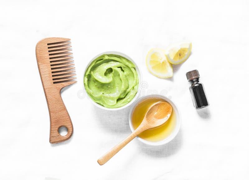 Avocado, maschera casalinga dei capelli del miele su fondo leggero, vista superiore Prodotti naturali per salute dei capelli fotografia stock libera da diritti