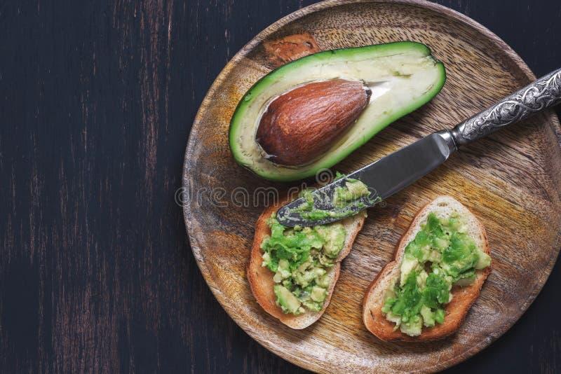 Avocado met toost op een houten plaat wordt gediend die Mening van hierboven royalty-vrije stock afbeeldingen