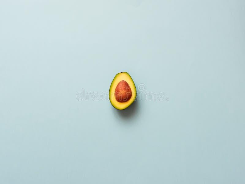 Avocado met zaad op blauwe achtergrond royalty-vrije stock afbeelding