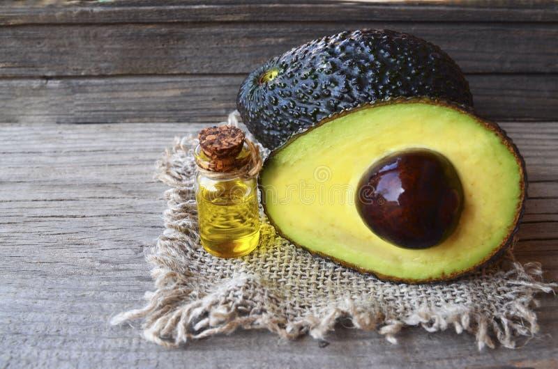 Avocado olej w małej szklanej butelce świeżym organicznie avocado na starym drewnianym tle i obrazy stock