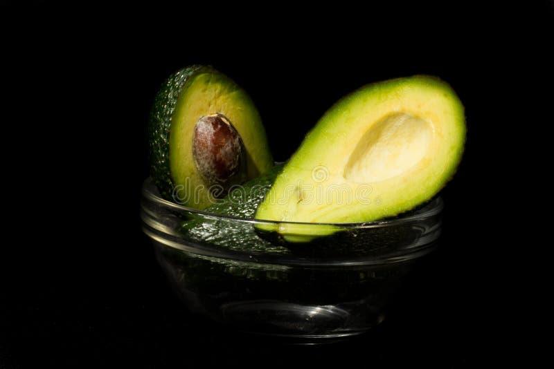Avocado op een zwarte achtergrond wordt geïsoleerd die stock afbeelding