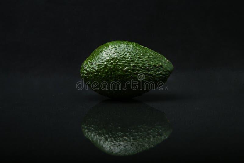 Avocado op zwarte achtergrond wordt geïsoleerd die stock foto