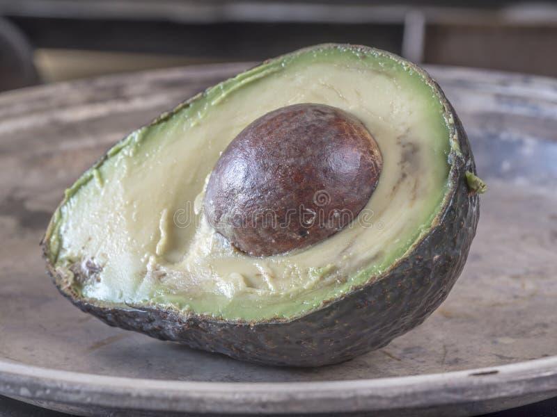Avocado, Persea Americana zur Hälfte auf Tabelle lizenzfreie stockbilder