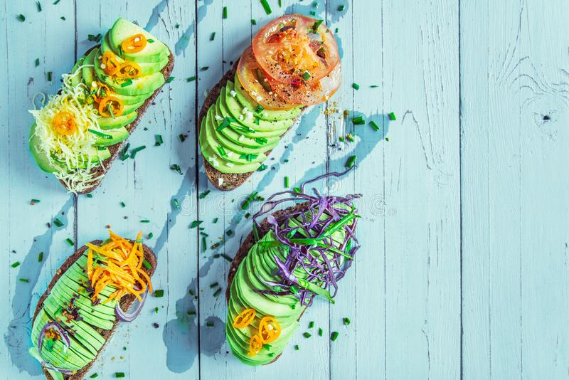 The avocado pieces on the crackling whole-grain bread with tomatoes, red cabbage, carrots and pepper strewed with green onions and royalty free stock photos