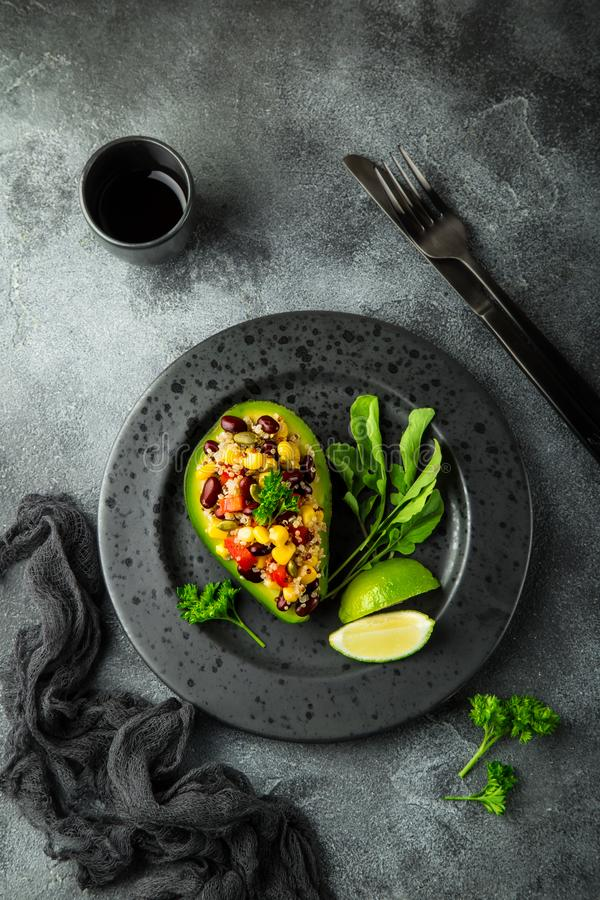 Avocado,quinoa, black bean, corn and bell pepper salad served. In avocado, top view royalty free stock photo