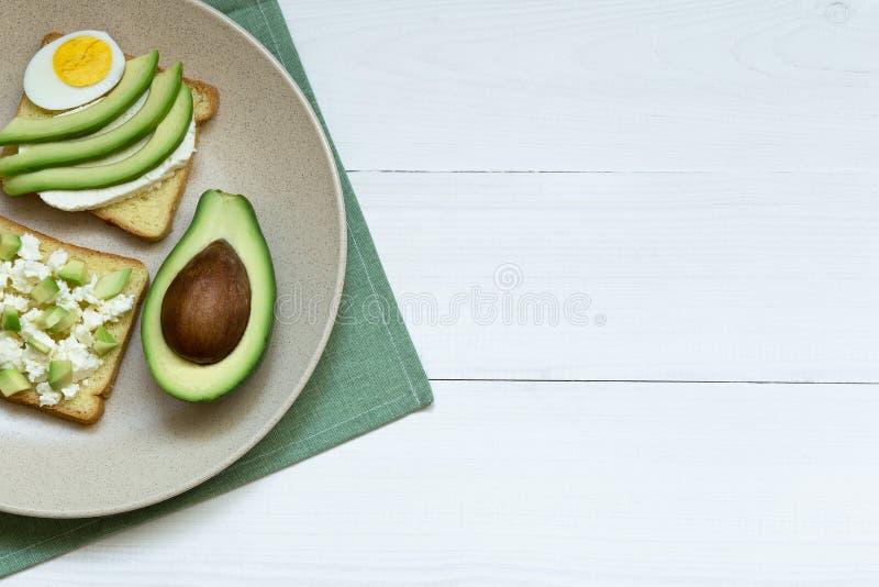 Avocado, ricotta, eisandwiches op ceramische plaat over witte houten achtergrond, hoogste mening, exemplaarruimte stock foto's