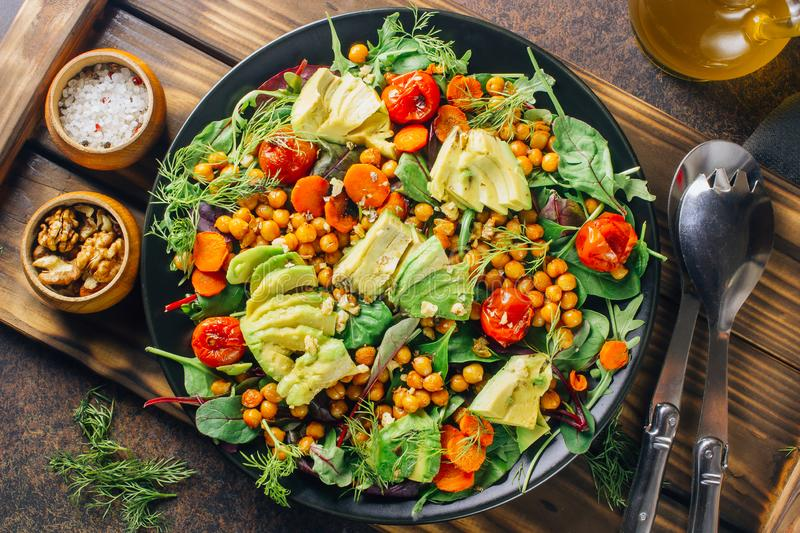 Avocado, roasted tomato, greens and chickpeas salad royalty free stock photography