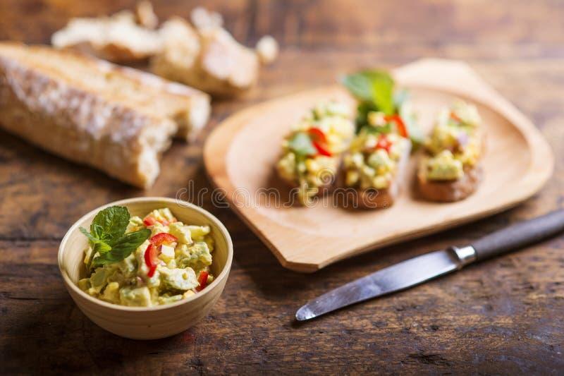 Avocado rozszerzanie się na plasterkach bruschetta przeciw drewnianemu stołowi obraz royalty free