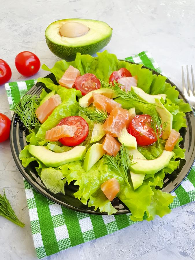 Avocado salad, salmon natural gourmet on a gray concrete background royalty free stock images