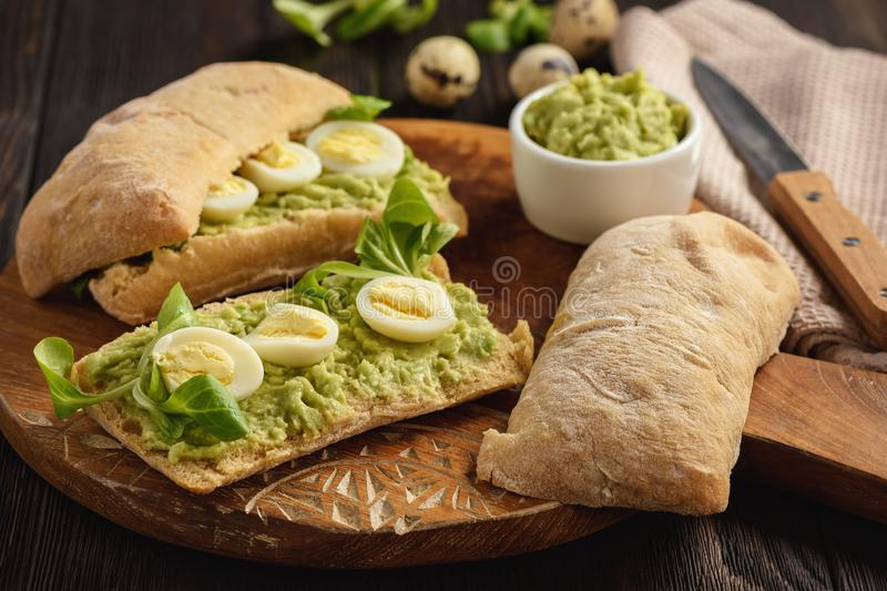 Avocado sandwich ciabatta with quail eggs. royalty free stock photos