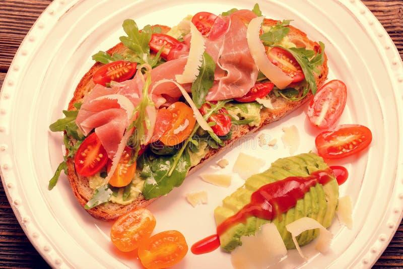Avocado sandwich on fresh bread with arugula stock photography