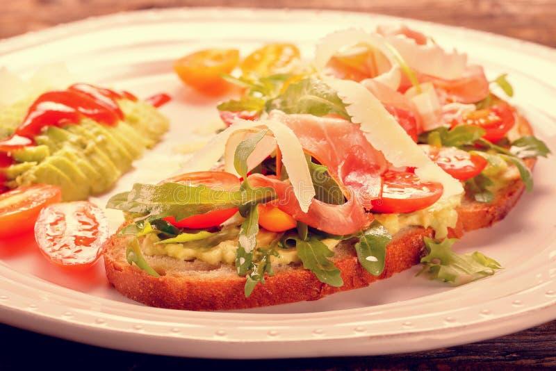 Avocado sandwich on fresh bread with arugula royalty free stock photos