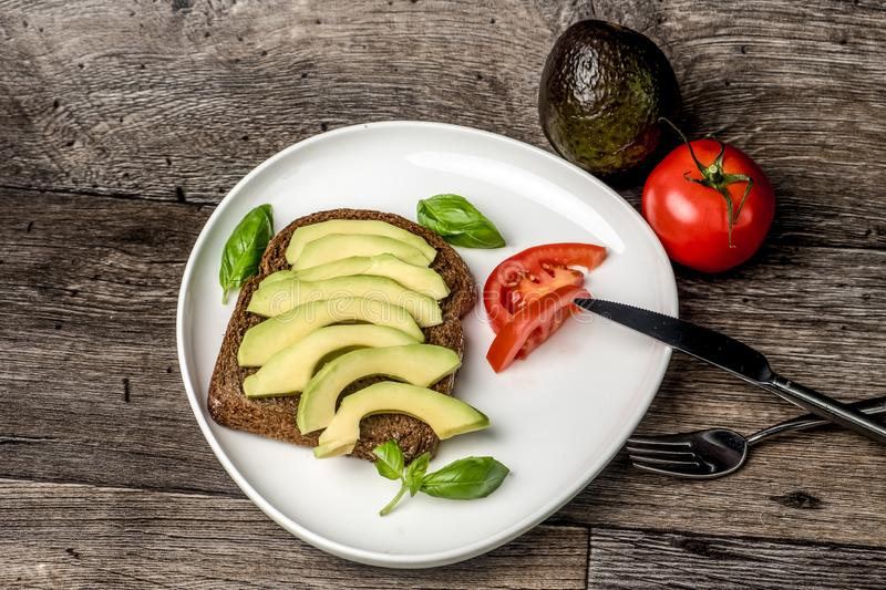 Avocado sandwich on a white plate and wooden table royalty free stock photo