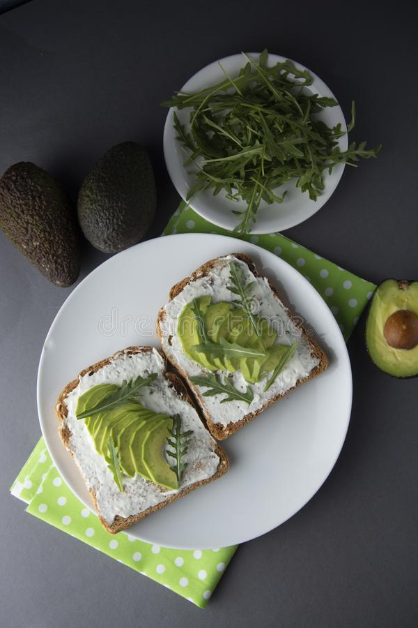 Avocado sandwich toast bread made with fresh sliced avocado, cream cheese. healthy food concept. Gray background. Food. Breakfast stock image