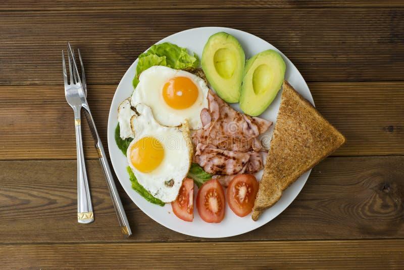 Avocado sano della prima colazione, panino delle uova con l'intero pane del grano su fondo di legno Copi lo spazio fotografia stock