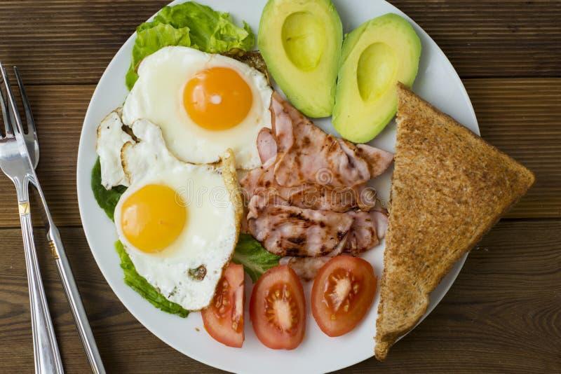 Avocado sano della prima colazione, panino delle uova con l'intero pane del grano su fondo di legno Copi lo spazio fotografia stock libera da diritti