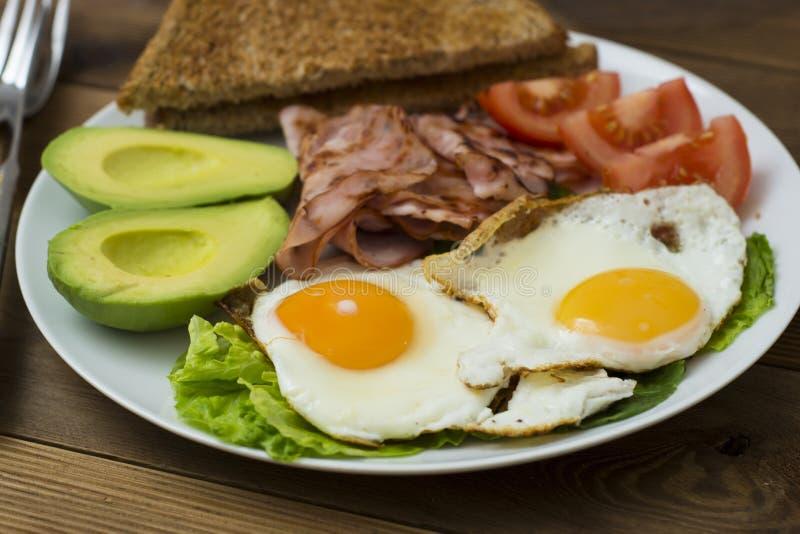 Avocado sano della prima colazione, panino delle uova con l'intero pane del grano su fondo di legno Copi lo spazio fotografie stock libere da diritti