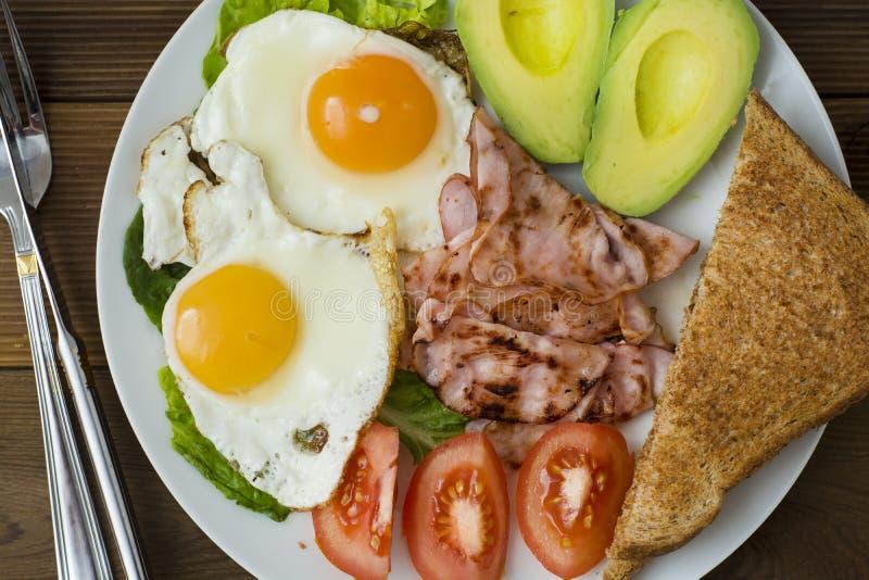 Avocado sano della prima colazione, panino delle uova con l'intero pane del grano su fondo di legno Copi lo spazio fotografie stock