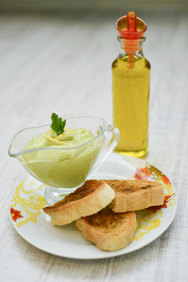 Avocado sauce. Creamy avocado pasta sauce with bruschetti and olive oil royalty free stock image
