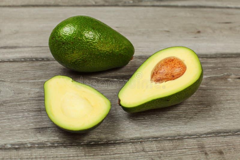 Avocado schnitt zur Hälfte mit ganzer Rückseite der Birne herein, auf grauer hölzerner Tabelle stockbild