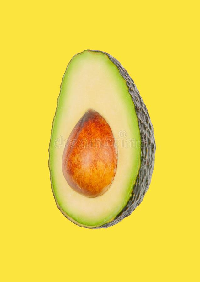 Avocado schweben in einer Luft auf gelbem Pastellhintergrund frei Konzept der Gem?selevitation stockfoto
