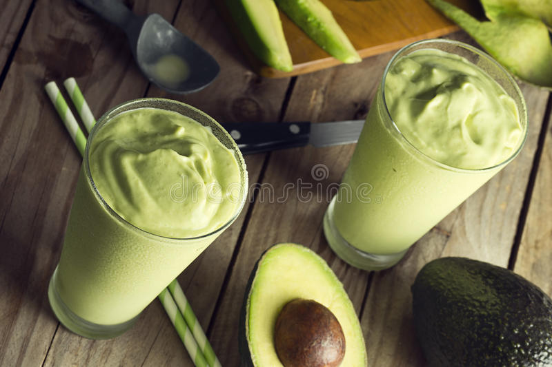 Avocado Shake or Smoothie Being Poured Into Glasses. Avocado shake or smoothie is being poured into two glasses. This sweet drink is made from avocados blended royalty free stock image