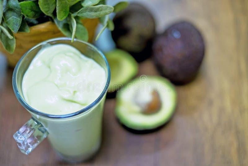 Avocado su un fondo di legno della tavola e frullato dell'avocado in un vetro immagine stock libera da diritti