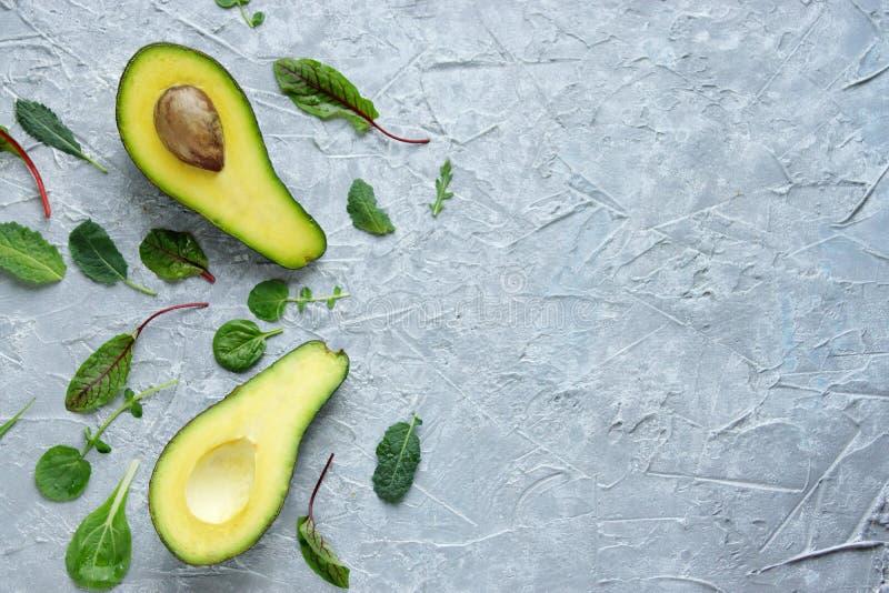 Avocado tagliato nelle mezze bugie su un fondo concreto grigio circondato dai dadi e dalle foglie dell'insalata verde, dieta dell fotografie stock libere da diritti