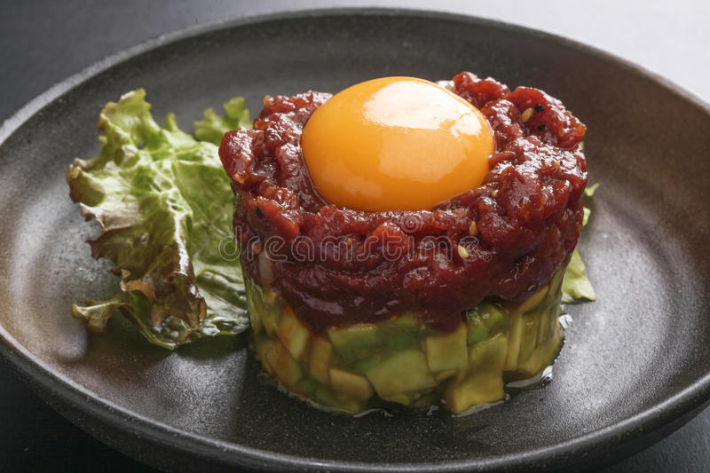 Avocado tartare stab Sakura beef meat with red egg and lettuce o. N black platter deliciously royalty free stock photo