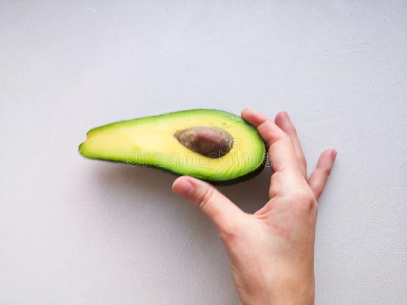 Avocado ter beschikking, op witte achtergrond Man die aan Vrouw met Overeenkomst Ring In Avocado voorstellen close-up De Avocado  stock afbeeldingen