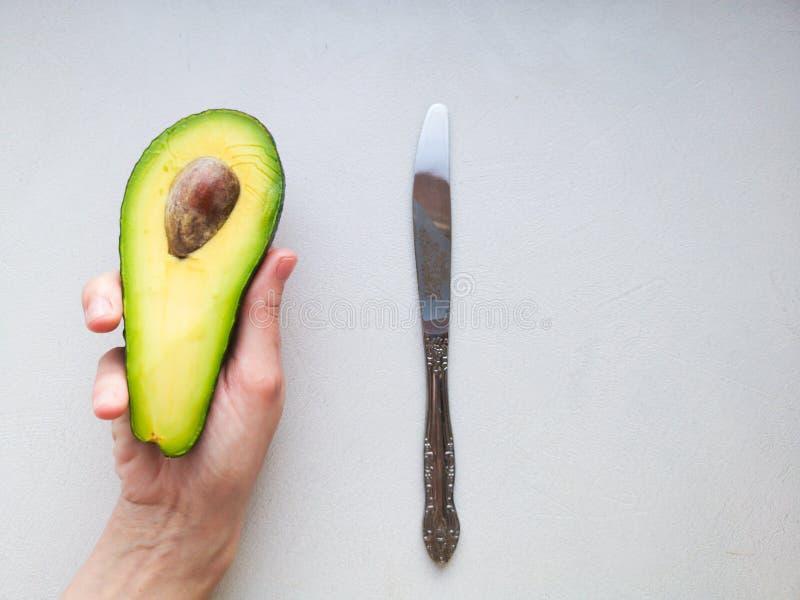 Avocado ter beschikking, op witte achtergrond Man die aan Vrouw met Overeenkomst Ring In Avocado voorstellen close-up De Avocado  stock foto