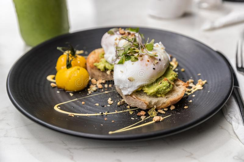 Avocado toast with eggs breakfast plate at restaurant closeup. Trendy healthy morning food at cafe with guacamole and poached egg stock photo