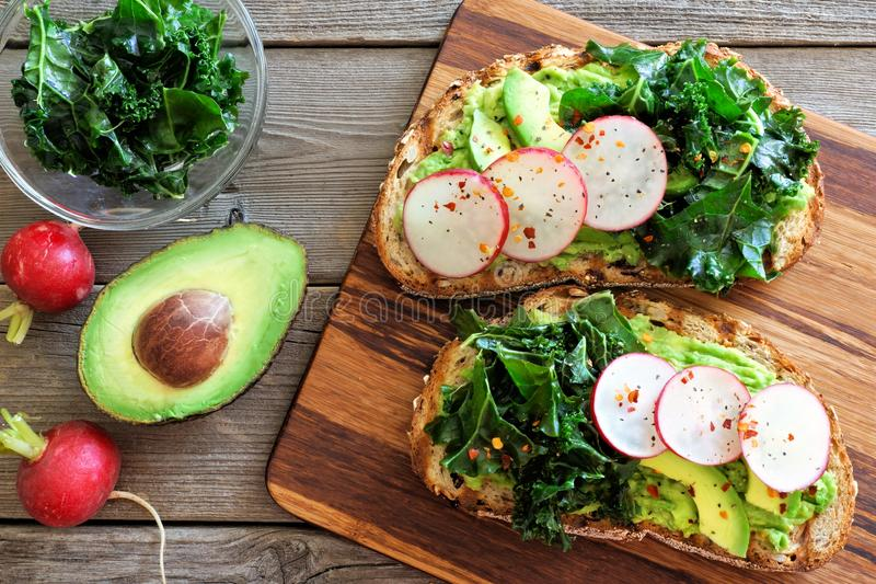 Avocado toast with kale and radish over rustic wood stock photography