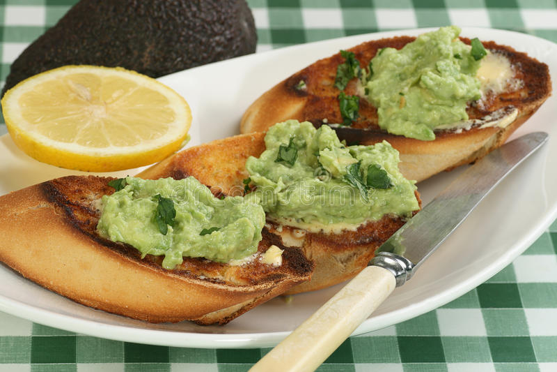 Avocado on toast. Mashed avocado with lemon and coriander on toasted crusty bread royalty free stock photography